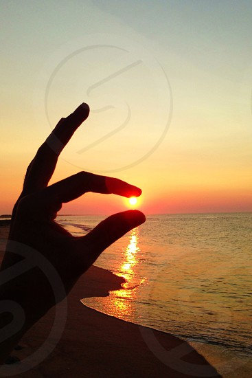 person trying to hold sun photo