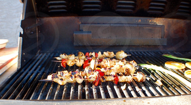 Grilling meats vegetables hot summertime outside kabobs barbecue  photo