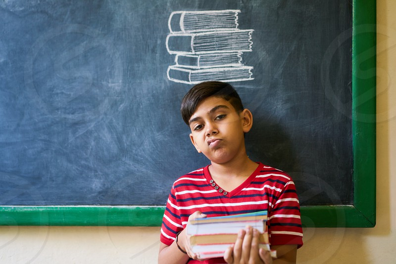 Concept on blackboard at school. Young people student and pupil in classroom. Sad and bored hispanic boy in class. Portrait of male child looking at camera holding books photo