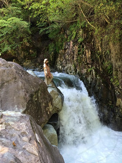 woman standing on the edge of the waterfalls photo