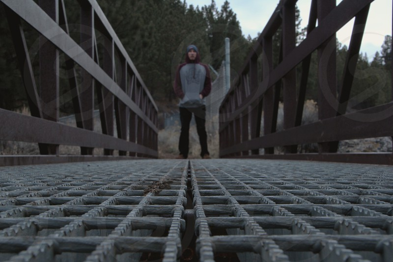 man standing on a wooden bridge photo