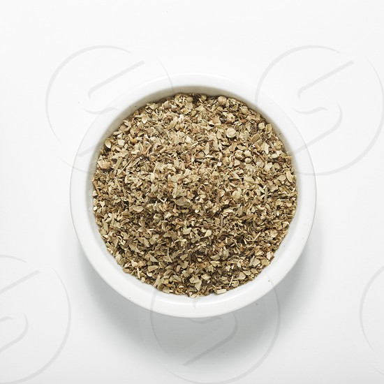 Bowl of dried oregano leaves isolated on white  top view photo
