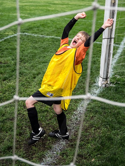 boy in yellow and black jersey tank top standing on soccer field photo