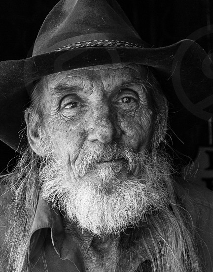 Friendly weathered old man in cowboy hat.  Close-up black and white portrait photo
