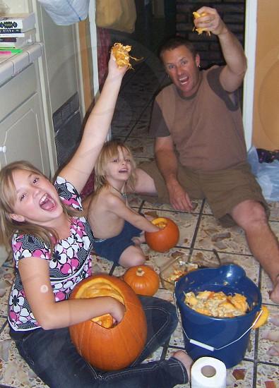 man and 2 girls shouting holding a pumpkin photo
