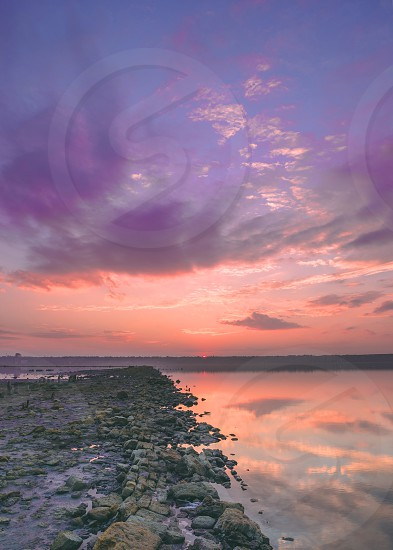 Sunset clouds over a drying salt lake photo