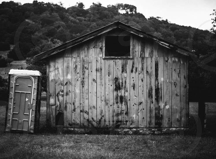 Black and white farm portapotty old garage weathered wood photo
