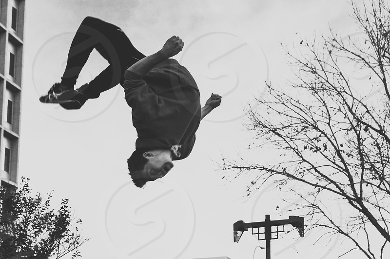 grayscale photo of man on back flip photo