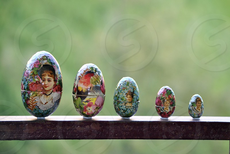 5 egg trinkets on brown wooden railing during daytime photo
