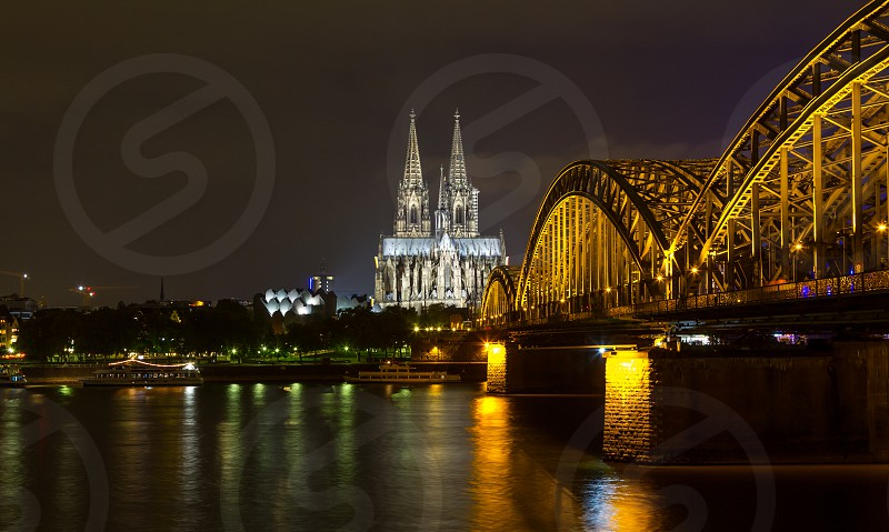Germany - Cologne/Köln Here is the postcard view from Cologne featuring the Dom cathedral and the old railway bridge (Hohenzollern) over the Rhine river. photo