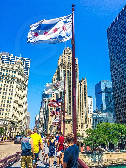 people walking on footbridge under Chicago flag during daytime photo