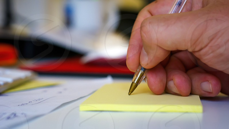 Male hand writing with a pen on a yellow sheet photo