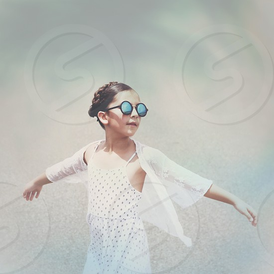 girl wearing white cardigan and sunglasses with both arms raised photo