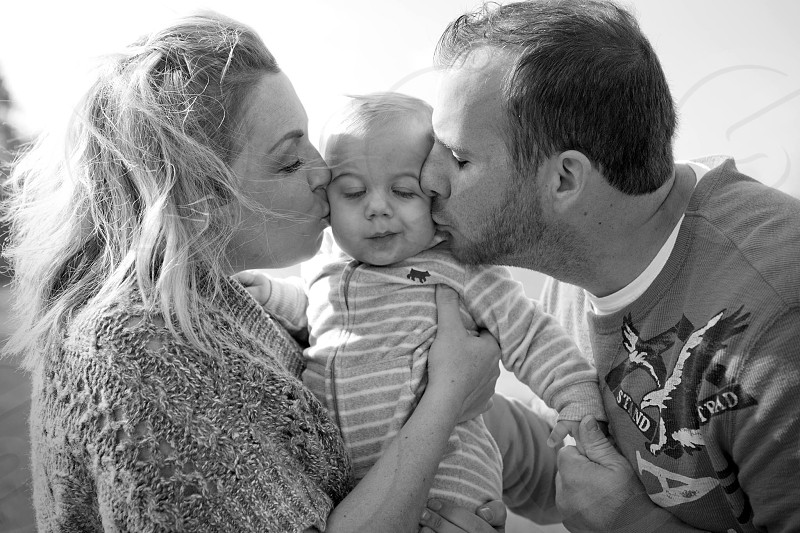 grayscale photo of couple kissing toddler photo