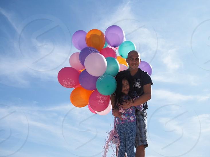 man hugging a girl holding balloons photo
