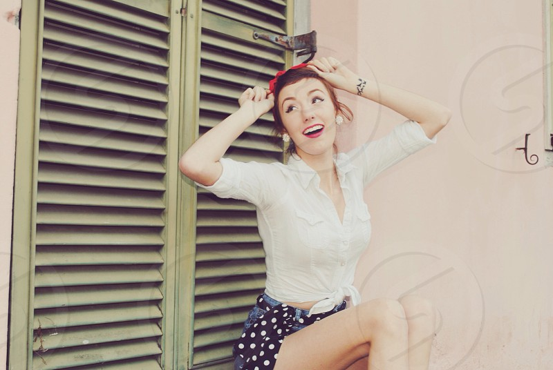 woman with brown hair in red scarf pin-up girl top and dotted black shorts in front of green shutters photo