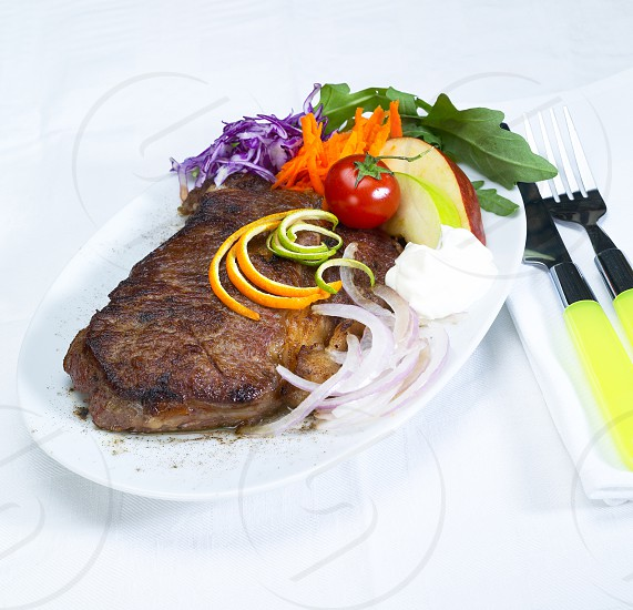 fresh juicy beef ribeye steak grilled with lemon and orange peel on top and vegetables beside with sour cream photo