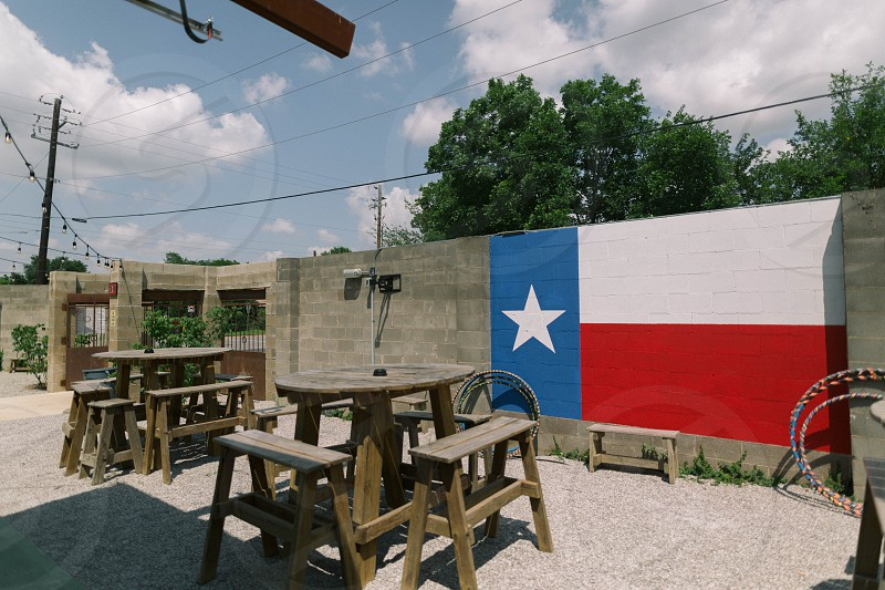 brown wooden stool beside tables with grey concrete wall with texas flag under white clouds and blue sky during daytime photo