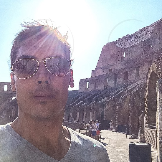 man in gray v-neck shirt and gold-framed sunglasses in front of antique architectural landmark during daytime photo