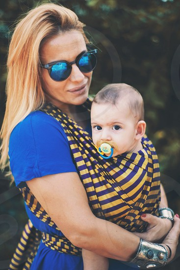 mom mother young youth baby child kid woven wrap stripes hug summer day blue dressface portrait photo