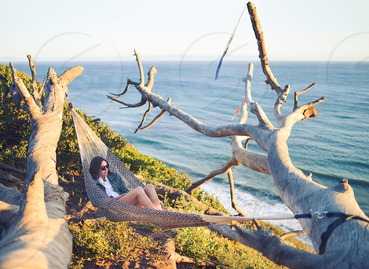 Woman sitting in hammock looking out to the sea photo