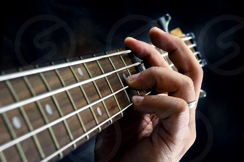 Closeup of guitarist hand holding a chord on the guitar fretboard photo