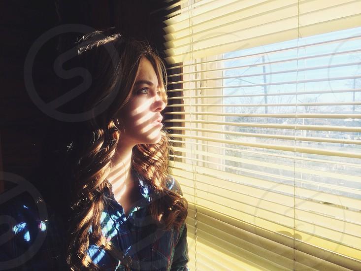 Blonde hair woman gazing through the window blinds photo