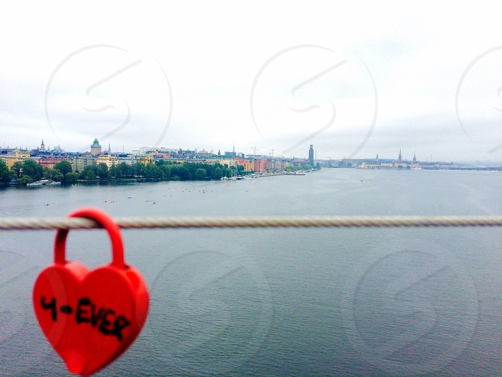 multicolored buildings by body of water view from rope with padlock photo
