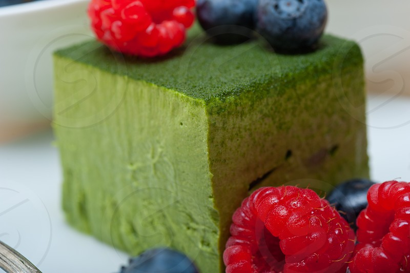 green tea matcha mousse cake with raspberries and blueberries on top photo