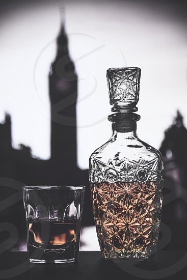 Whiskey in a glass with vintage bottle and London in the background. photo