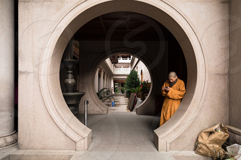 China Shanghai a buddhist monk in Jingan temple checking his mobile phone circle round religion buddhism pray building photo