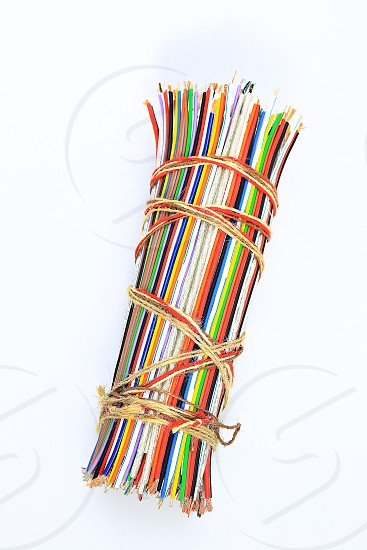 "Topic:""Bundle of Wires"" 5  This is an image of a bundle of electronic wires in multiple colors tied up with string with copy space and a clean white background. photo"