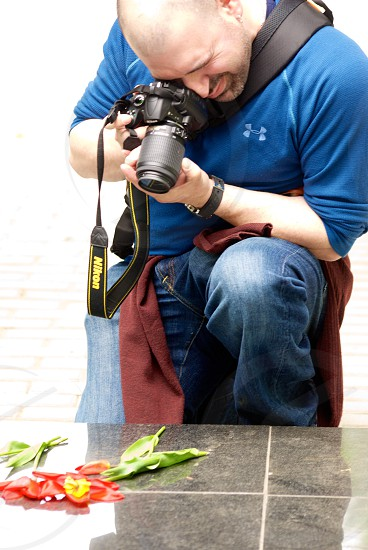Shooter shooting a photo of flowers placed upon a tomb for those lost in World War II.  photo