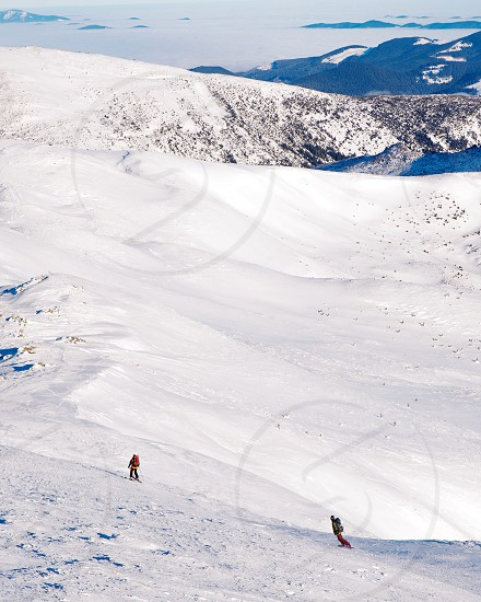 skier and snowboarder ride in snowy mountains photo