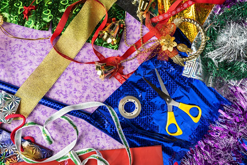The process of packing Christmas holiday gifts. Wrapping paper ribbon Christmas decorations. View from above closeup view. Handmade. photo