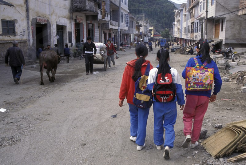 childern on the way to school  in the town of Yangshou near the city of  Guilin in the Province of Guangxi in china in east asia.  photo