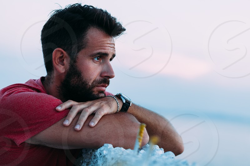 Young sad man by the sea looking at horizon photo
