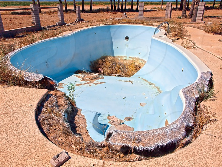 An abandoned swimming pool in the Arizona desert near the Eagle Tail Mountains in Harquahala Valley. The home this pool belonged to had burned down long ago and only the pool and the surrounding Palm Trees survived. photo