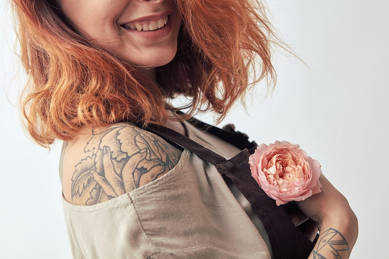Smiling girl with a tattoo holds in her hand a pink flower Rununculus on a gray background. Mother's Day Valentine's Day photo