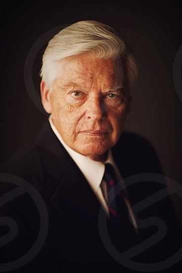 man wearing black formal suit and blue necktie photo