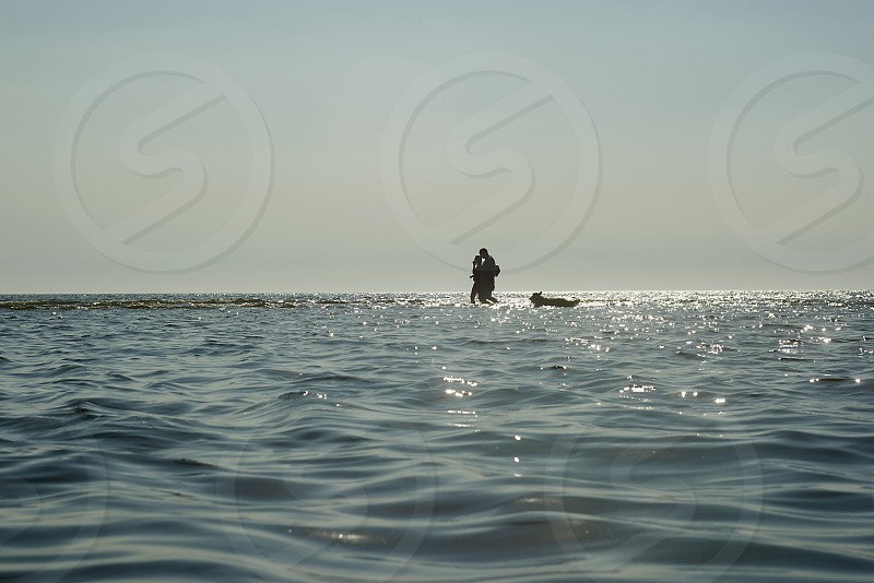 Silhouette of a man and child and dog walking in shallow water along the ocean front with sunlight glistening photo