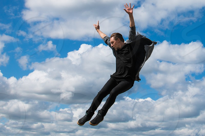 Flying jumping man dancer black clouds heaven in the air handsome human air falling photo