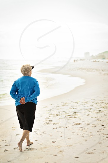 Elderly woman walking on the beach early in the morning.  photo