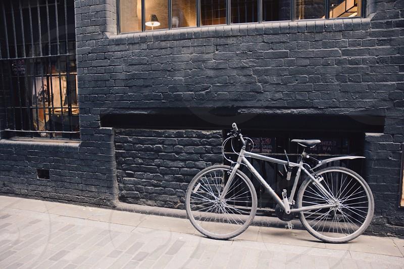gray bicycle near gray bricks wall photo