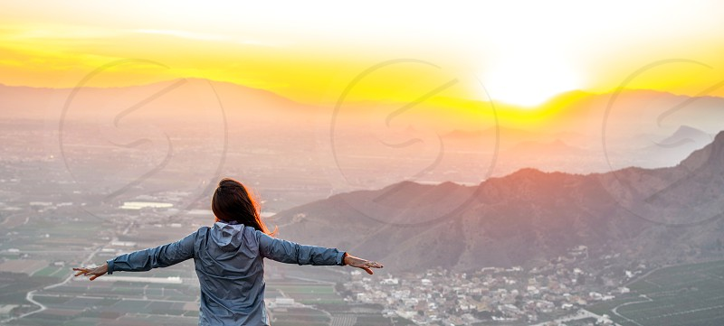 Woman in the montains with open arms at the sunset above cityscape photo