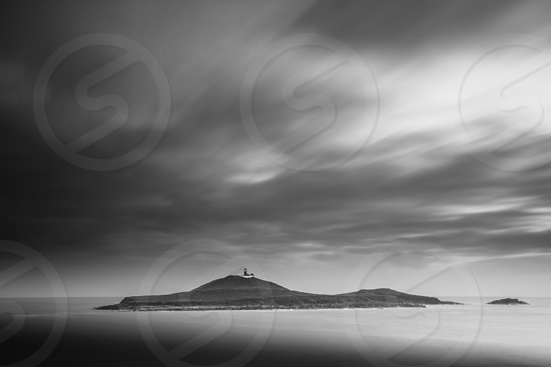 gray-scale photograph of cloudy sky above mountainous island photo