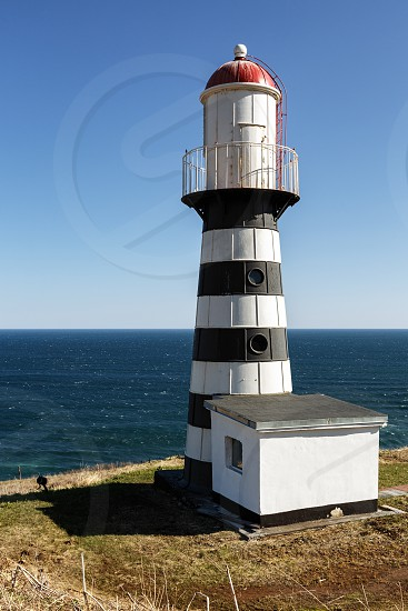 Petropavlovsky Lighthouse (founded in 1850) - oldest lighthouse in Russian Far East located on Cape Mayachny on Kamchatka on shore of Avacha Gulf in Pacific Ocean in vicinity of Petropavlovsk City. photo