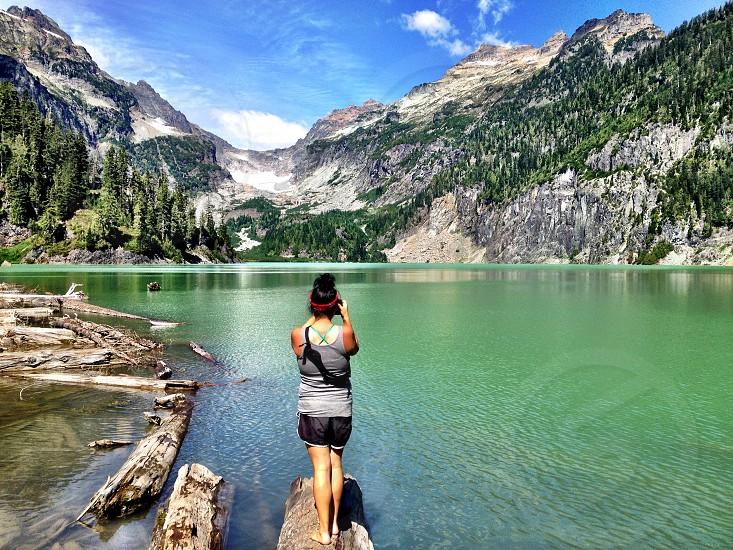 person wearing grey tank top standing on rock beside lake photo