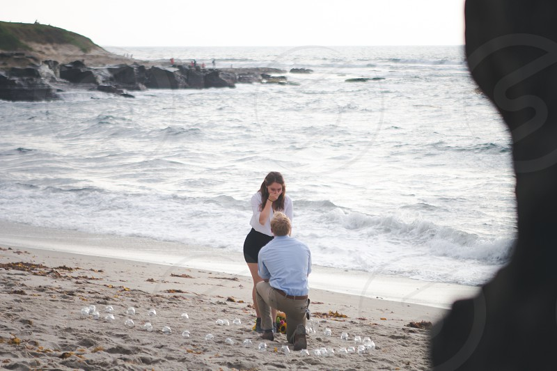 man proposing to woman on knee beside beach under white sky photo