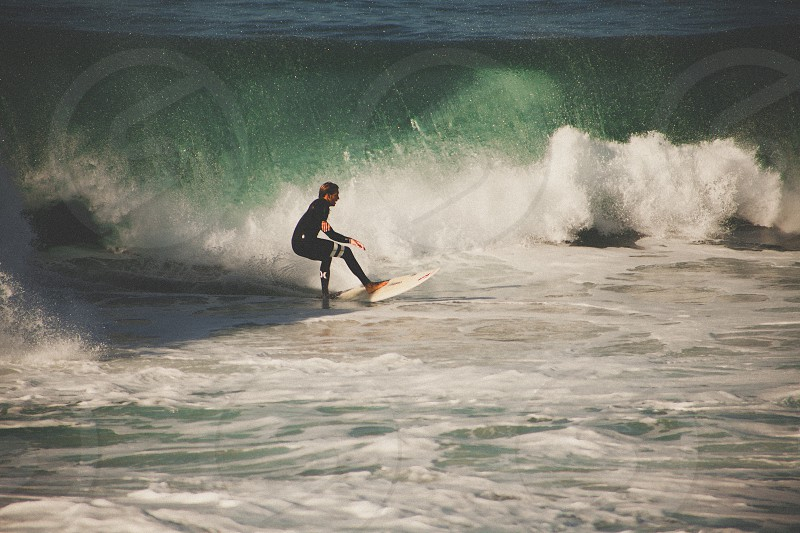 person in black wet suit riding surfboard photo